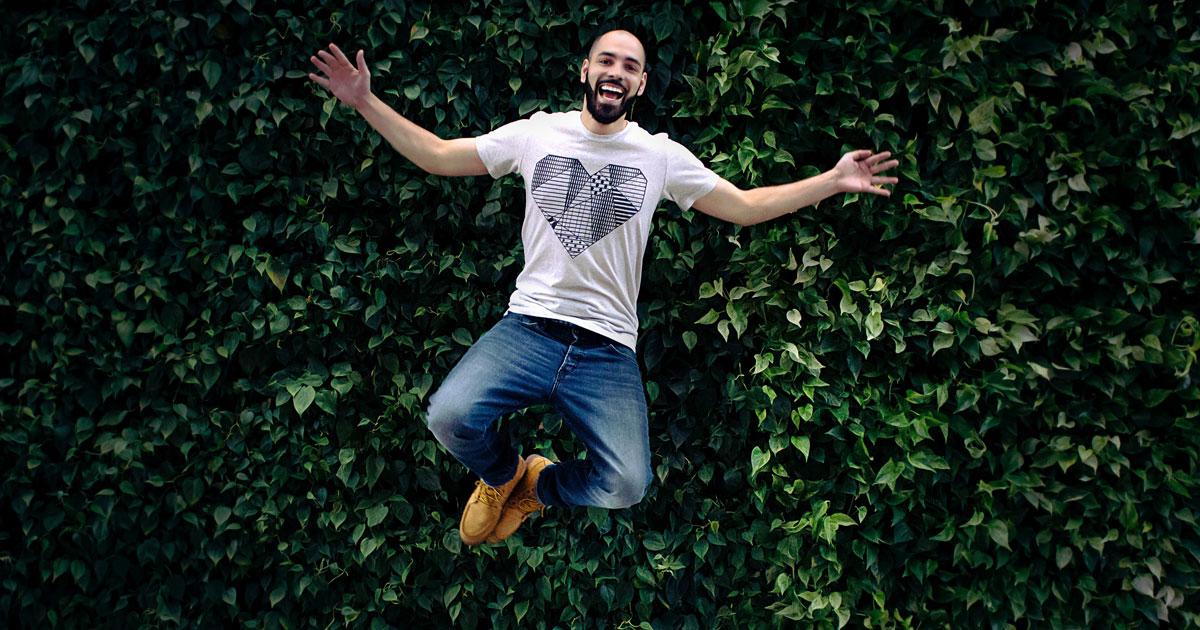 Person upphoppad i luften framför stor grön buske, ler och sträcker ut händerna och böjer på benen.