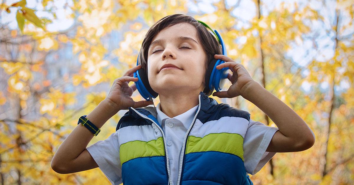 Barn som står i skogen och har på sig hörlurar