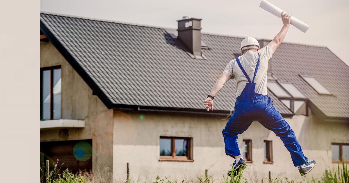 Person som fått beviljatt bygglov hoppar av glädje med planen i handen