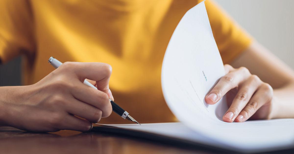 Händer som skriver på en tentamen för att bli diplomerad registrator