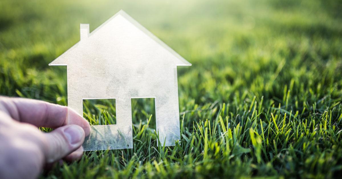 En utklippt siluette i genomskinlig plast av ett hus som hålls över en mark