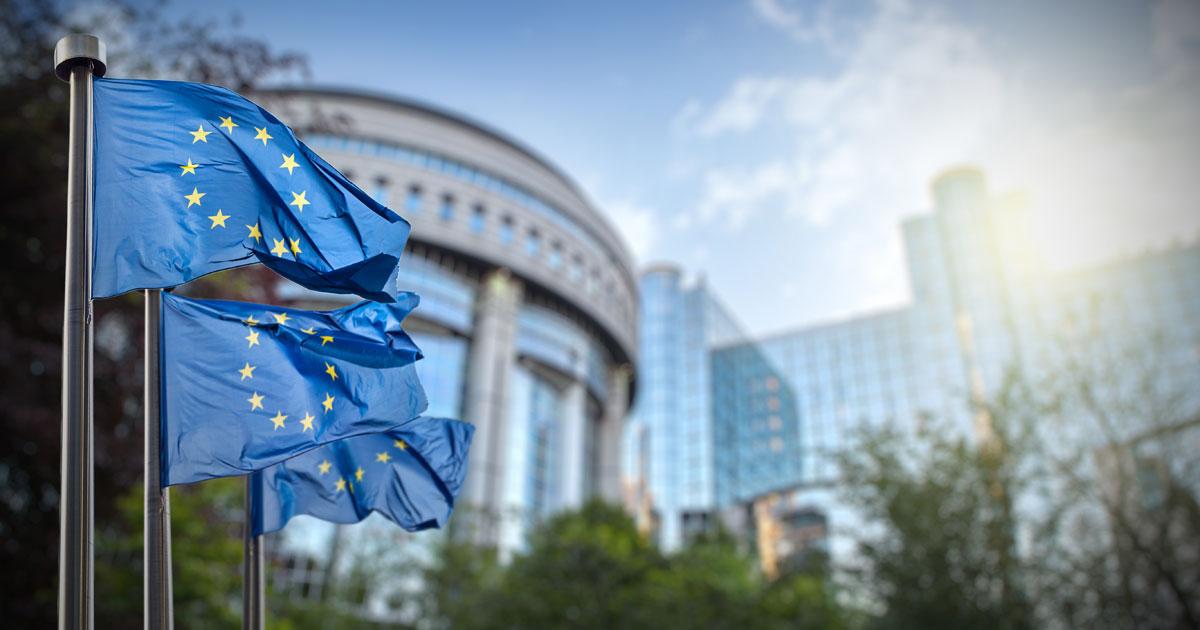EU-flaggor i förgrunden och EU-kommistionen i bakgrunden