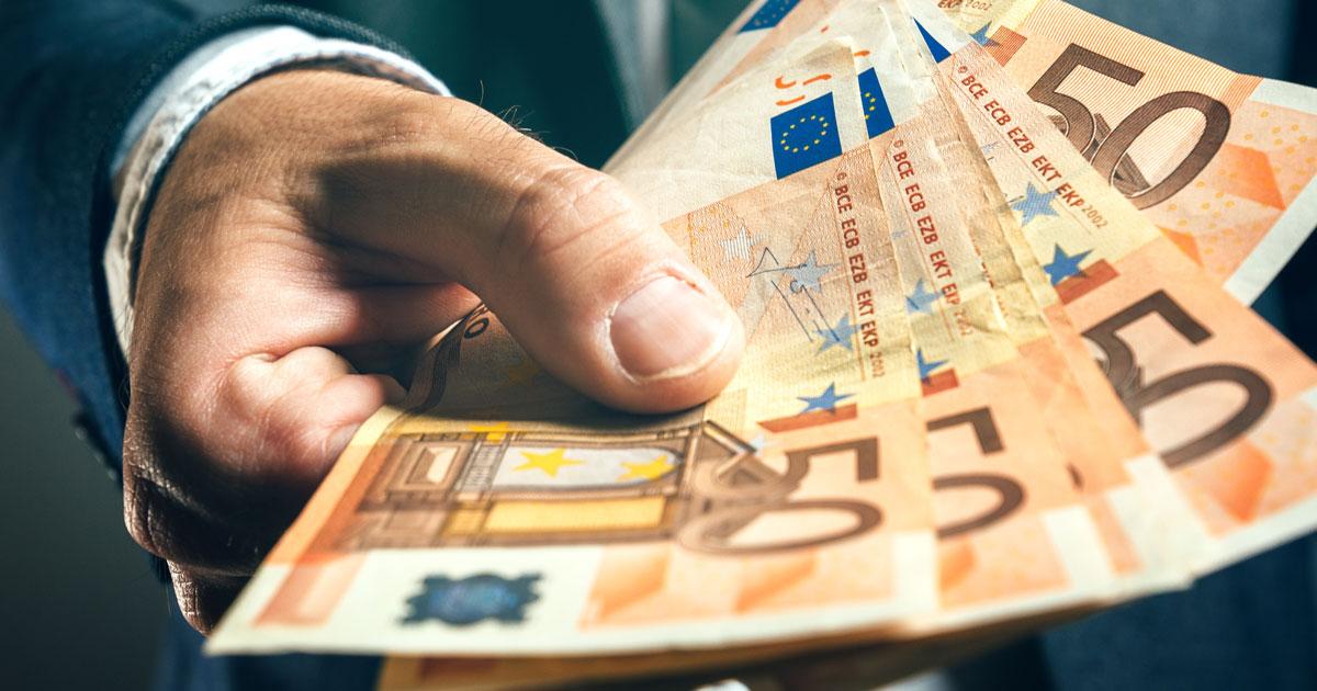 Hand som håller i en bunt med eurosedlar
