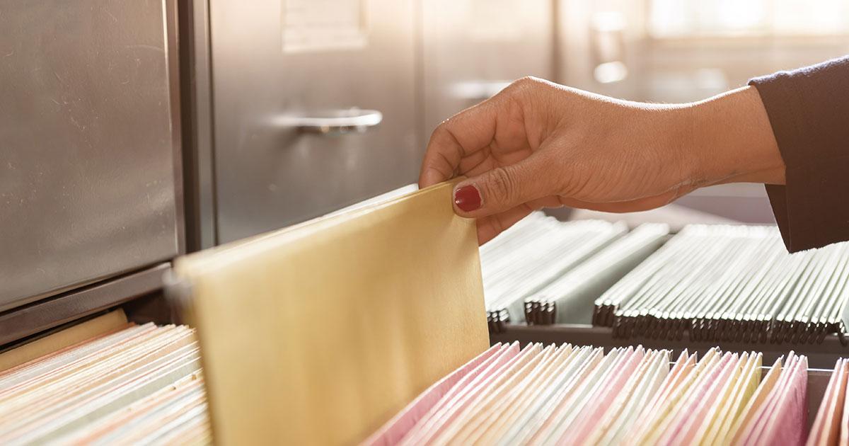Hand som drar upp ett dokument ur ett diarieskåp