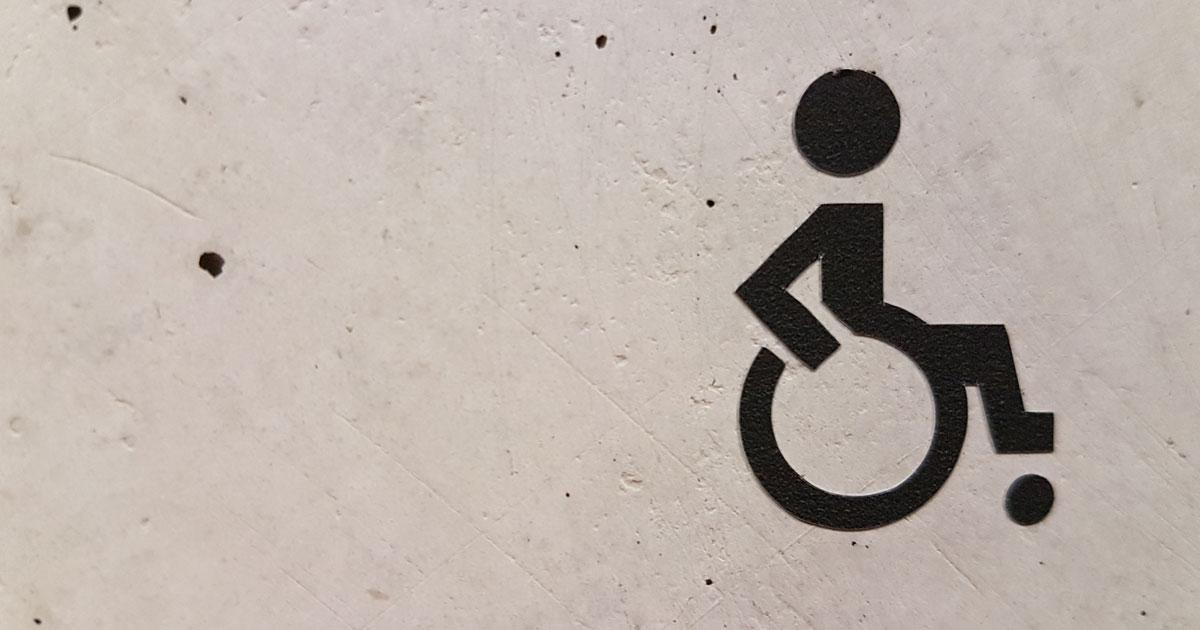 Betongvägg med stencil av person som sitter i en rullstol