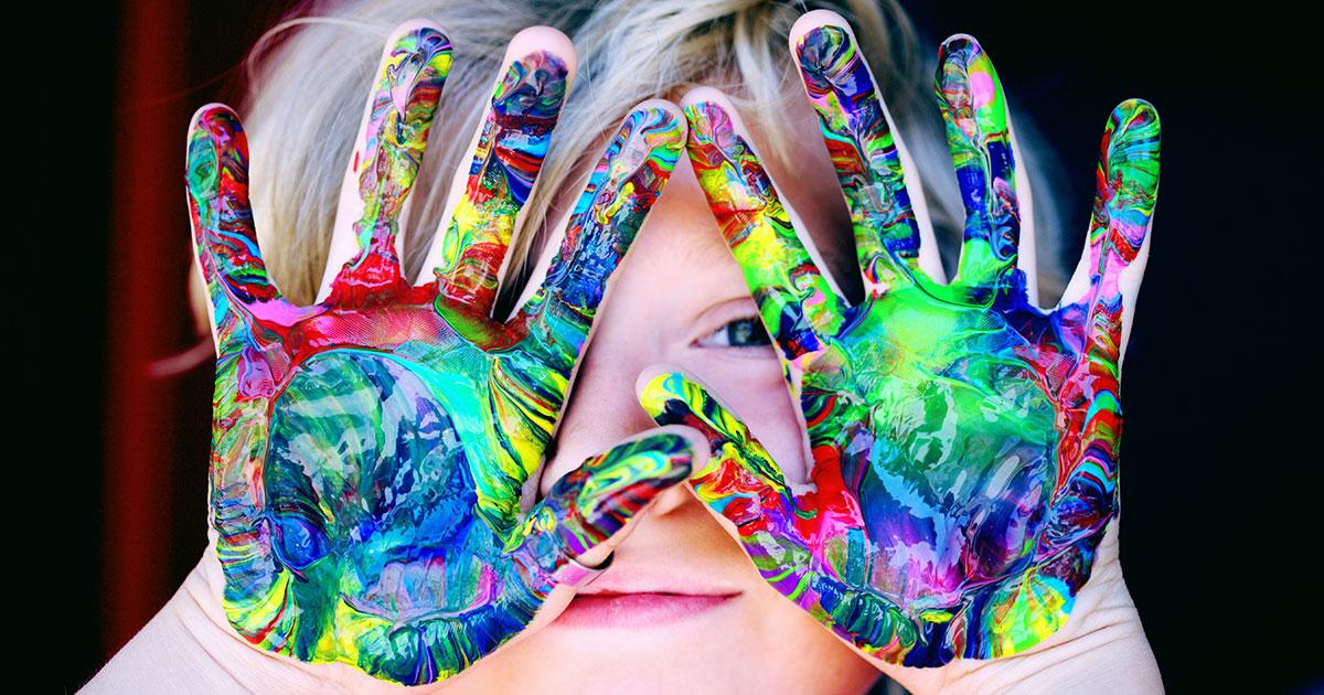 Barn som håller upp händer fulla av färg framför sitt ansikte