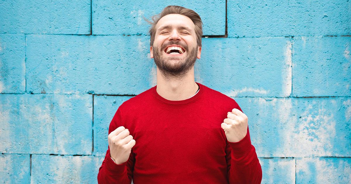 Person står framför blå vägg och knyter händerna, blundar och ler