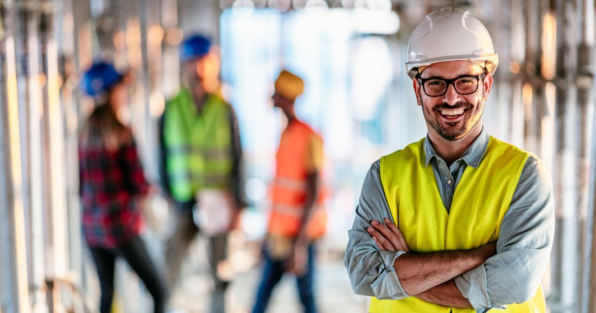 Byggarbetare på arbetsplats med säkerhetsklädsel