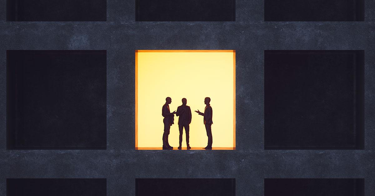 Tre personer står i ett upplyst fönster och diskuterar