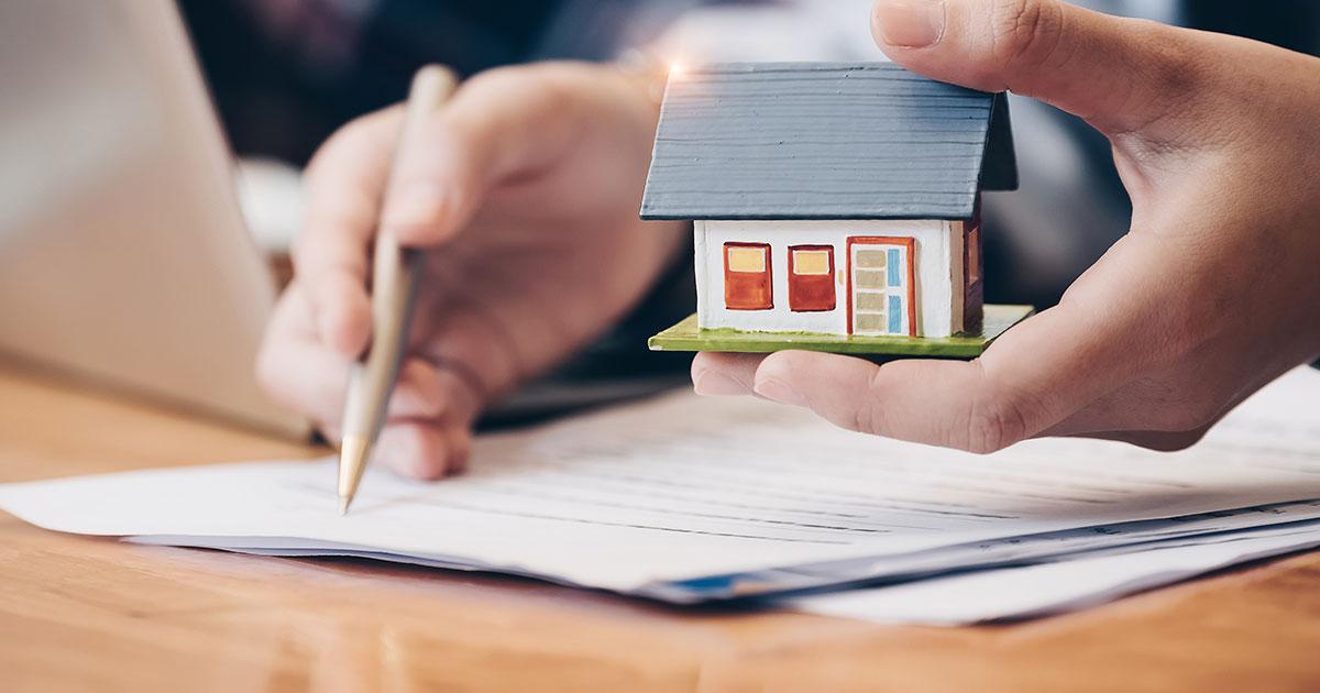 Hand som håller i ett litet modellhus medans den antecknar med den andra handen