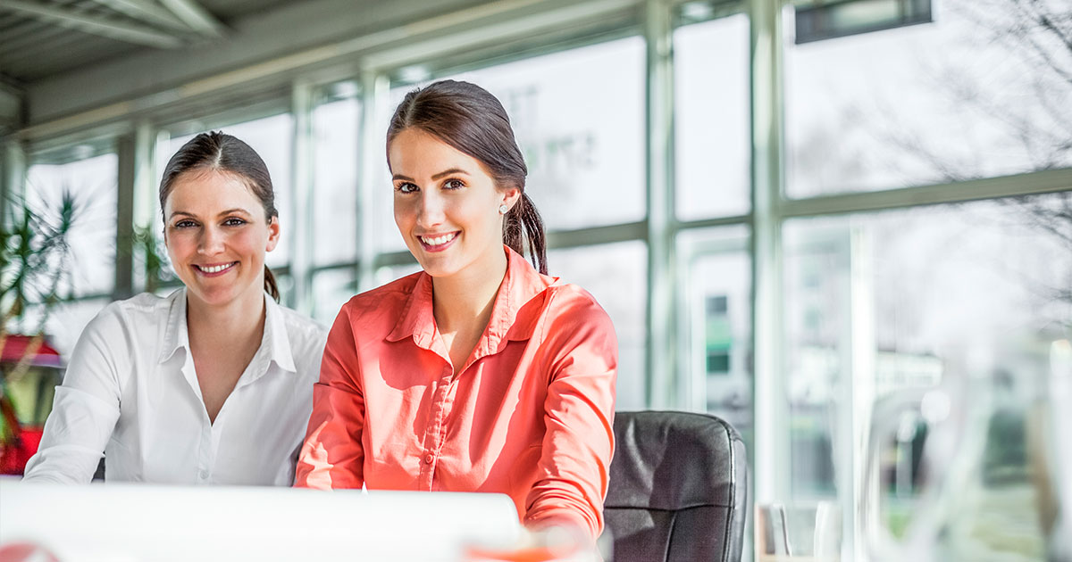 Två sekreterare som studerar juridik framför datorskärm