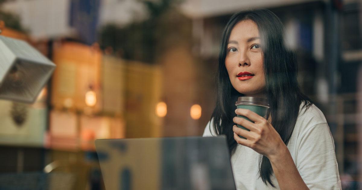 Person som sitter vid laptop och dricker kaffe på ett cafe