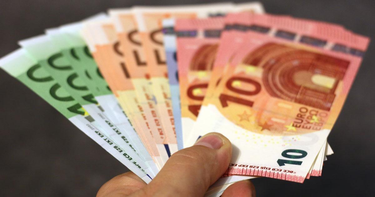 En hand som håller flera eurosedlar i en solfjädersform
