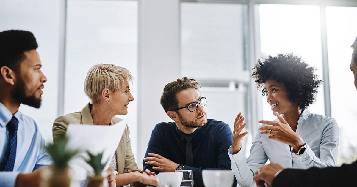 Grupp människor som lyssnar på sekreterare som samordnar arbetet