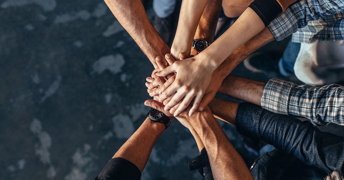 Flera personers händer som lagts ovanpå varandra
