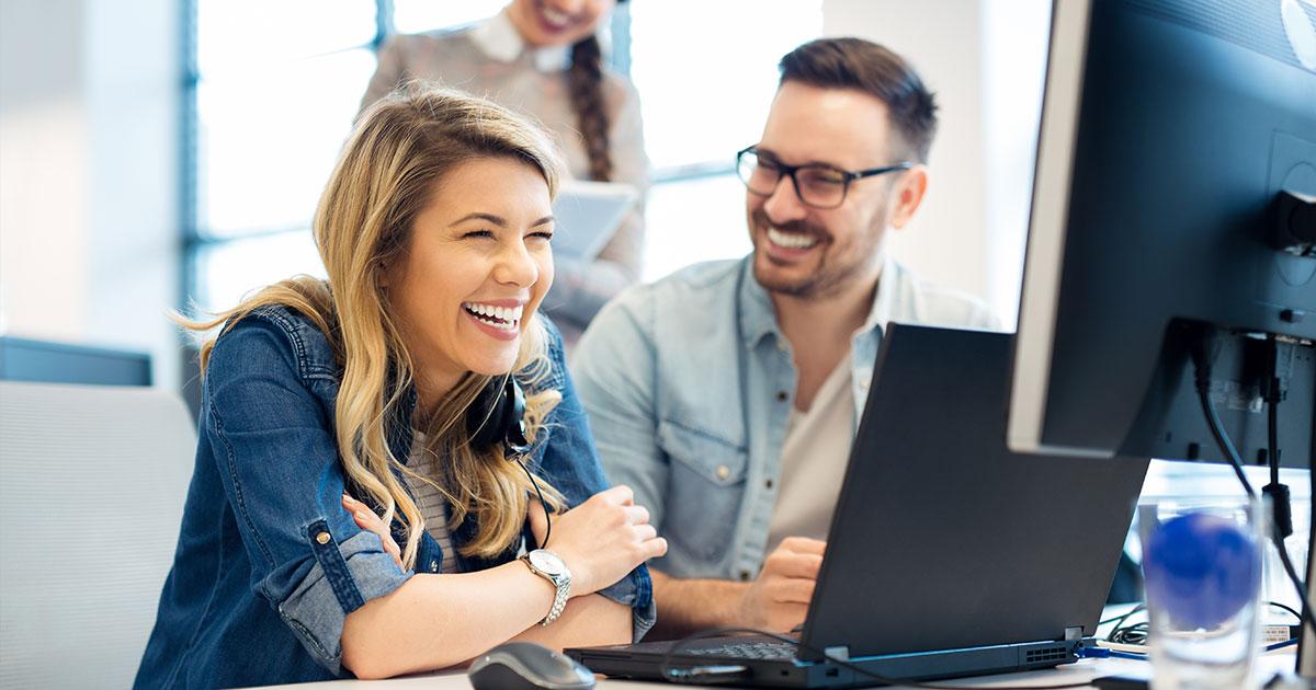 Två personer delar datorskärm och skrattar tillsammans vid utbildningstillfälle