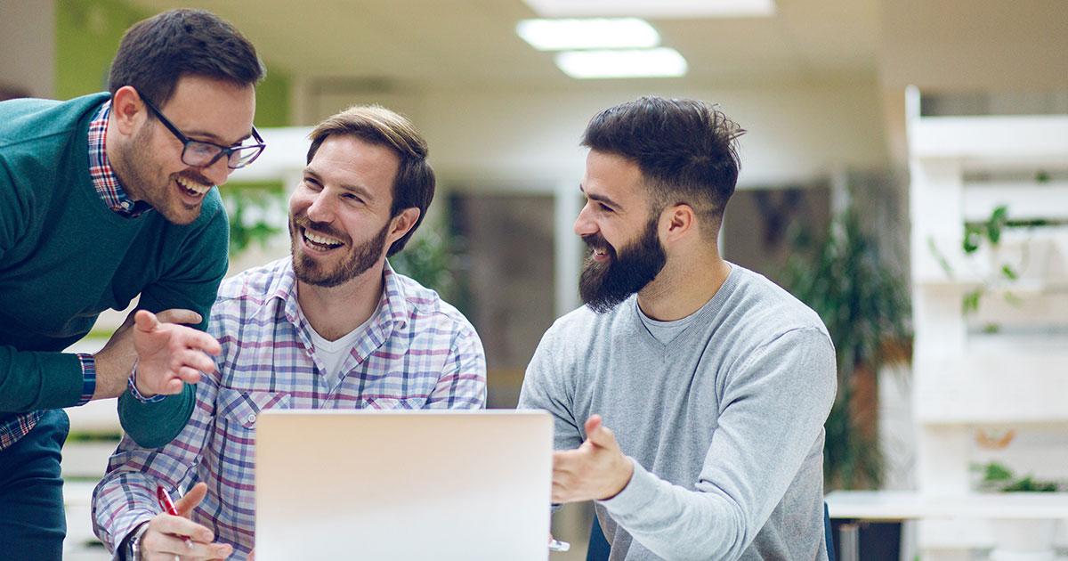 Tre personer skrattar och diskuterar vid bärbardator