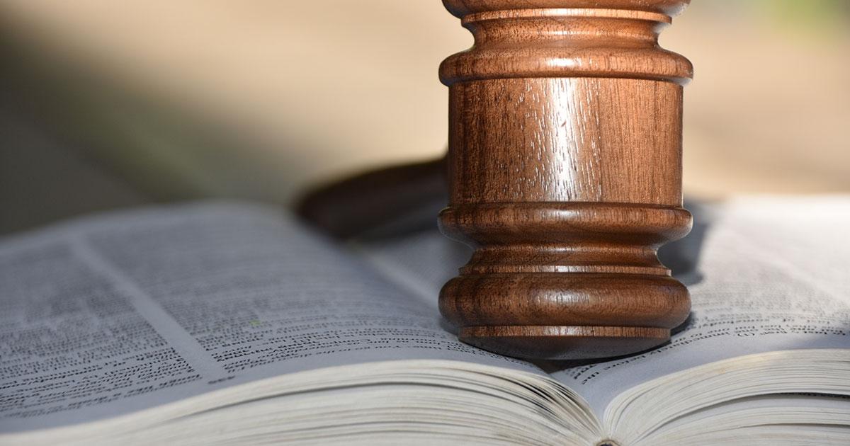 Lagbok uppslagen med en dommarklubba som bokvikt