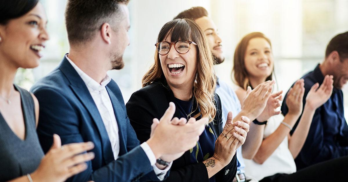 Sex personer som sitter på rad och klappar händer och ler
