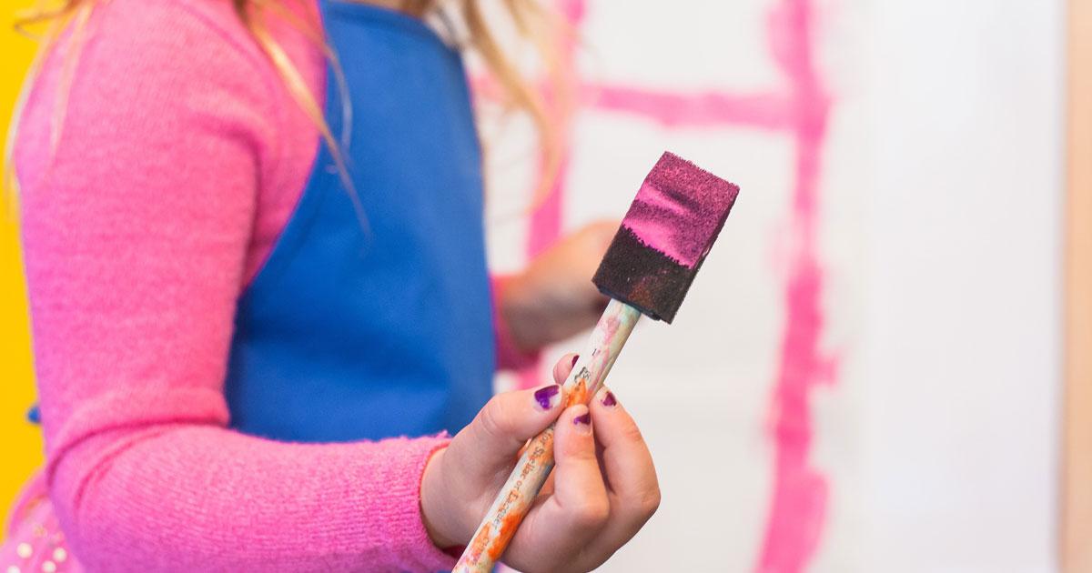 Elev i grundskolans om målar rosa med en pensel