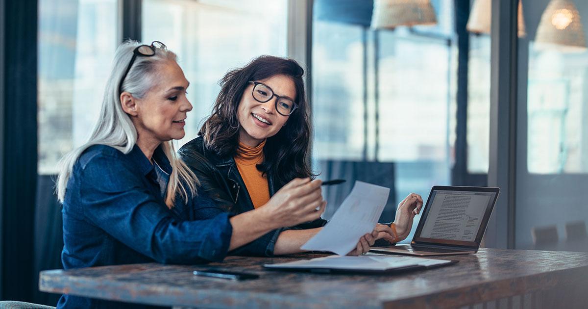 Två personer sitter vid ett grått bord och diskuterar och tittar på papper och laptop