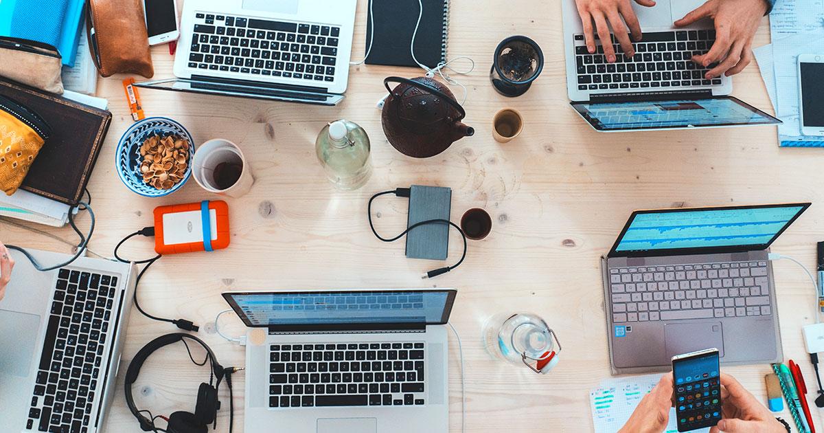 Översikt över bord fylld med händer som skriver på tangentbord och telefoner