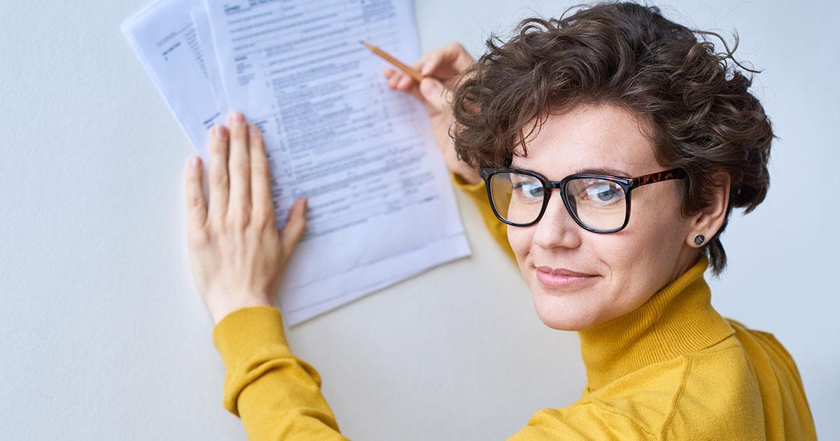 Person i gul tröja signerar papper