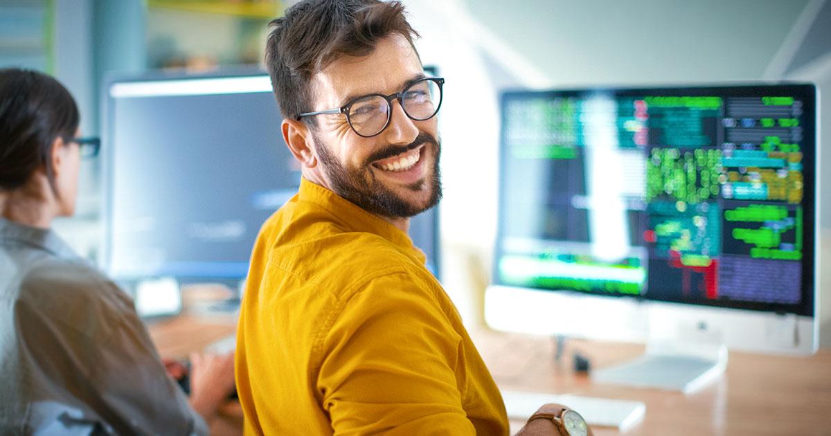 Person sitter ivid skärm och programerar och tittar över axeln och ler