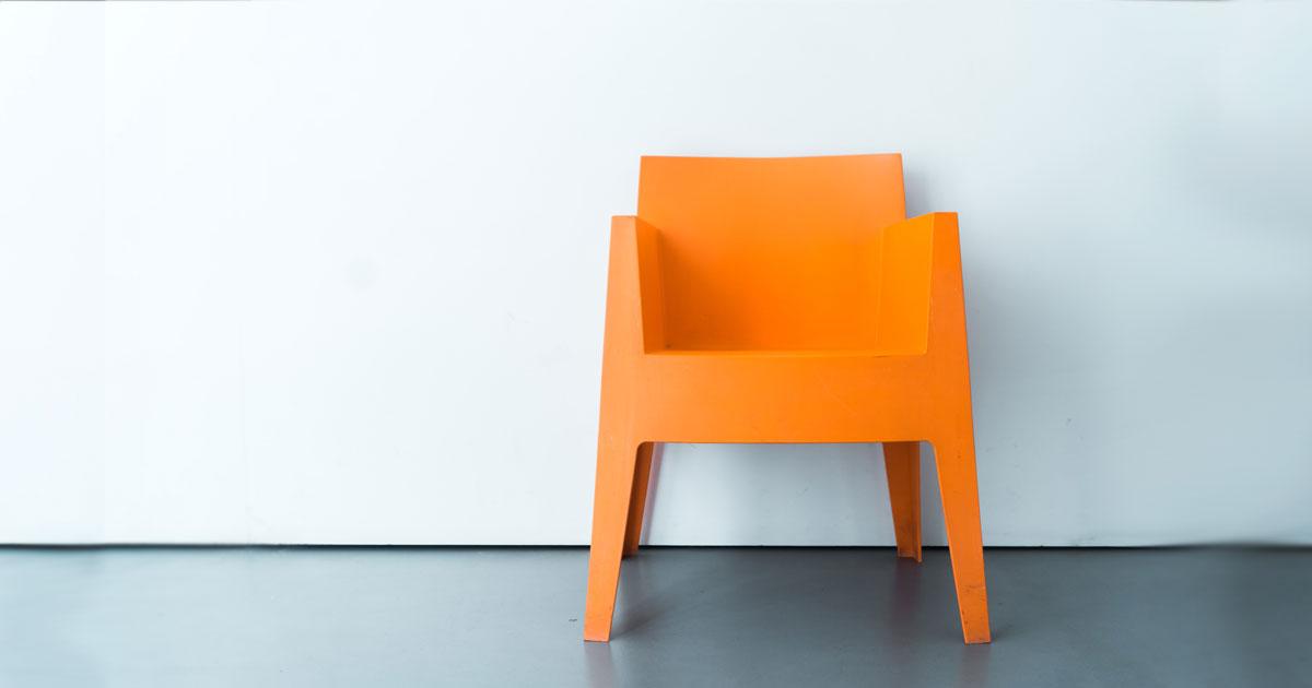 Orange stol som står ensam med vit bakgrund
