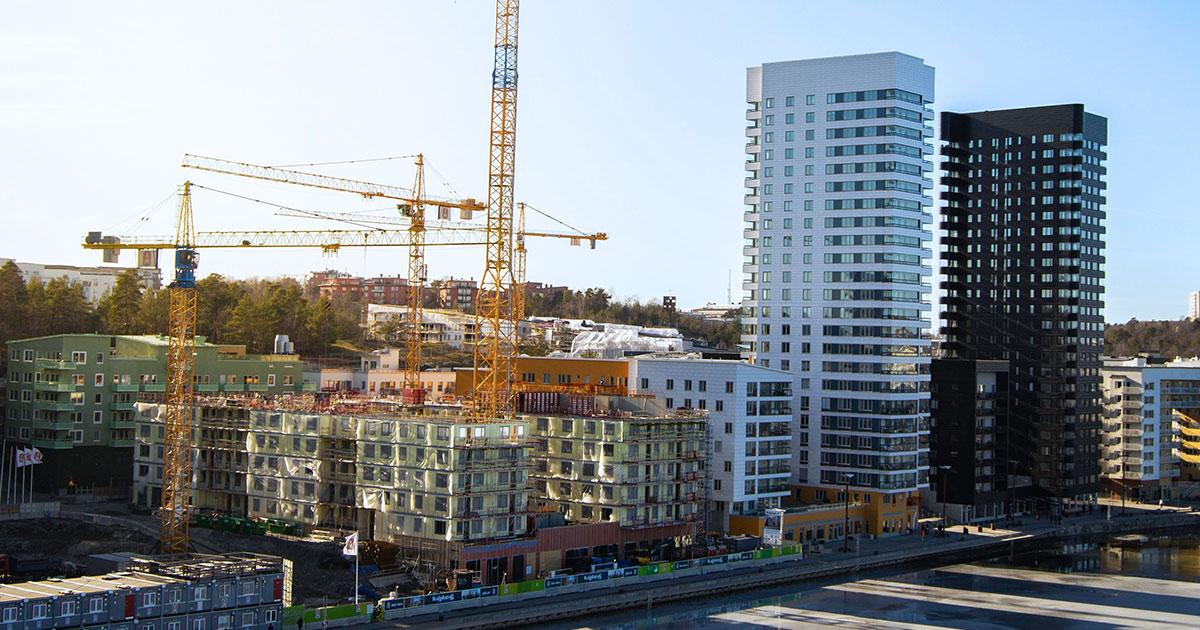 Bostadsområde som växer fram med höga hus och lyftkranar och byggställningar