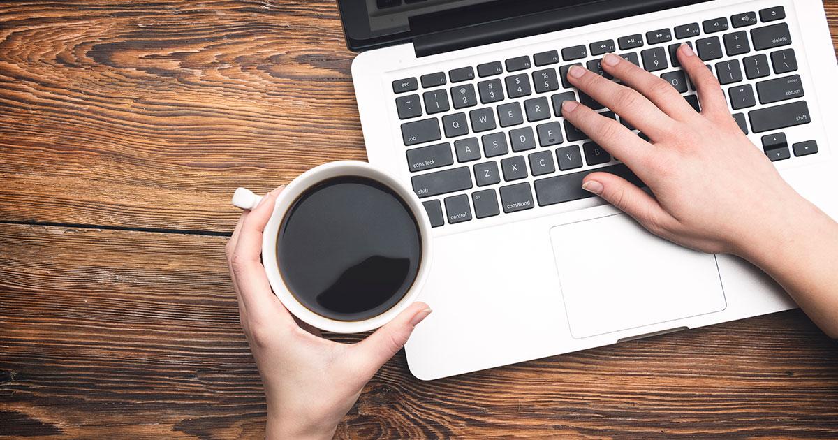 Bild från ovan på en hand som skriver på laptop och håller en kopp kaffe i den andra handen