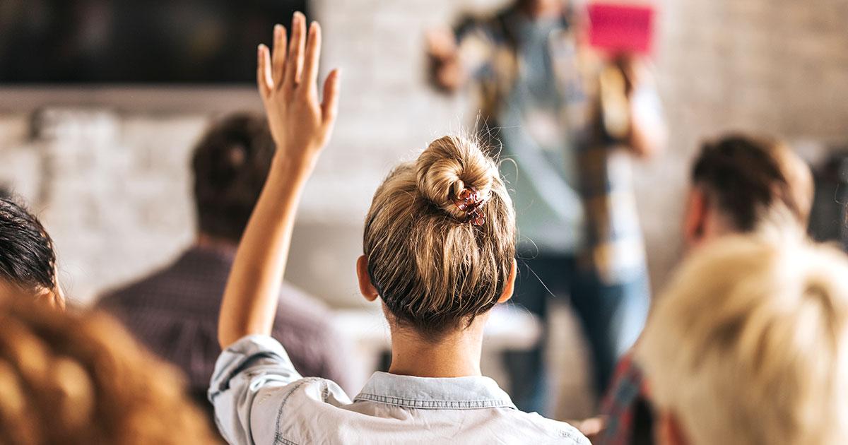 Elev som räcker upp handen med ryggen mot kameran