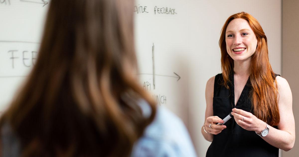 Person som vågar presentera ideér för medarbetare vid white board