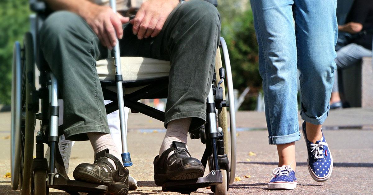 Hemtjänstpersonal som går bredvid rullstolsburen äldre patient