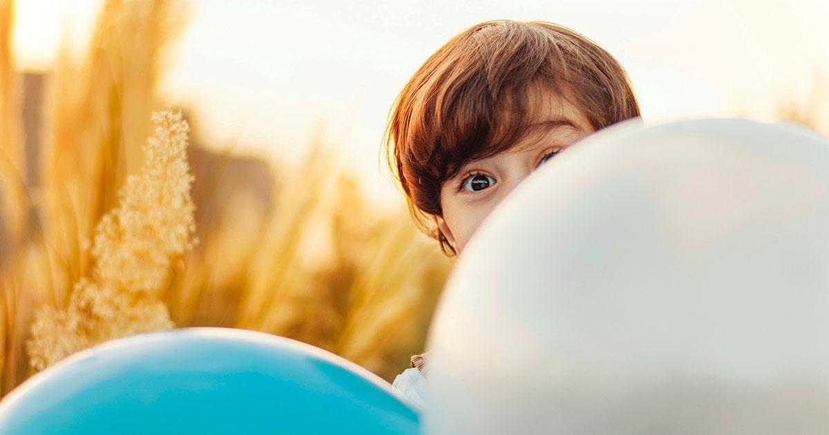 Barn som söker skydd bakom ballonger