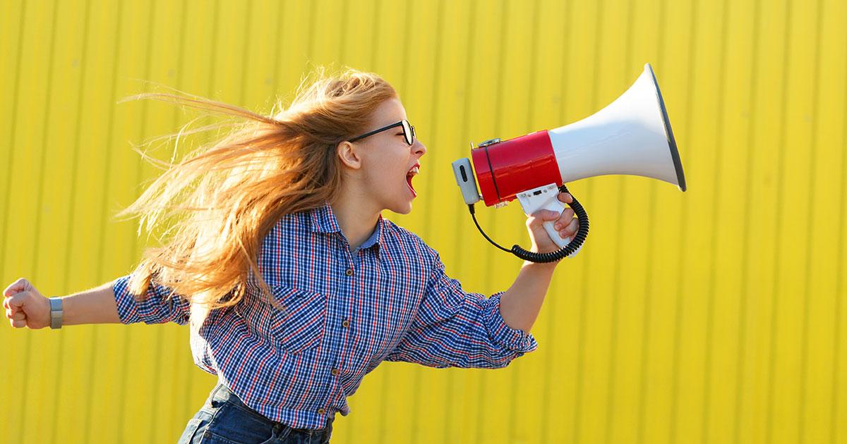 Kvinna står framför gul vägg och i motvind skriker hon i en megafon