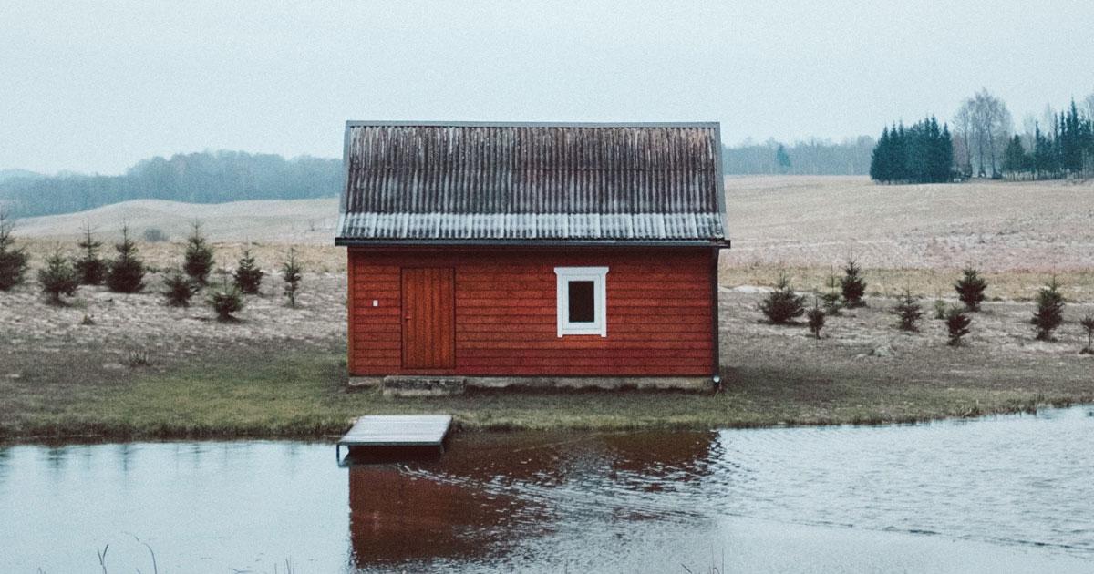 Ett rött trähus vid ett vattendrag med åkrar bakom