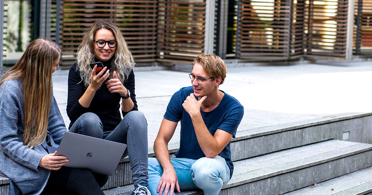 Tre personer sitter utomhus och samtalar vid laptop