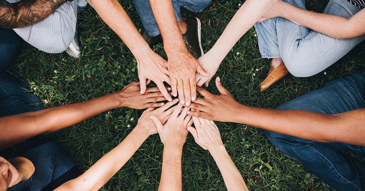 Flera personer vars händer sträcks ut och hålls ihop tillsammans