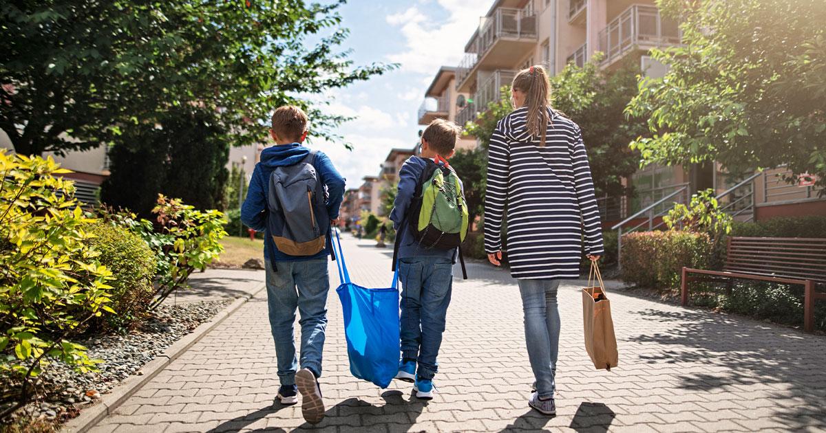 Tre personer i en familj som tillsammans bär en stor kasse