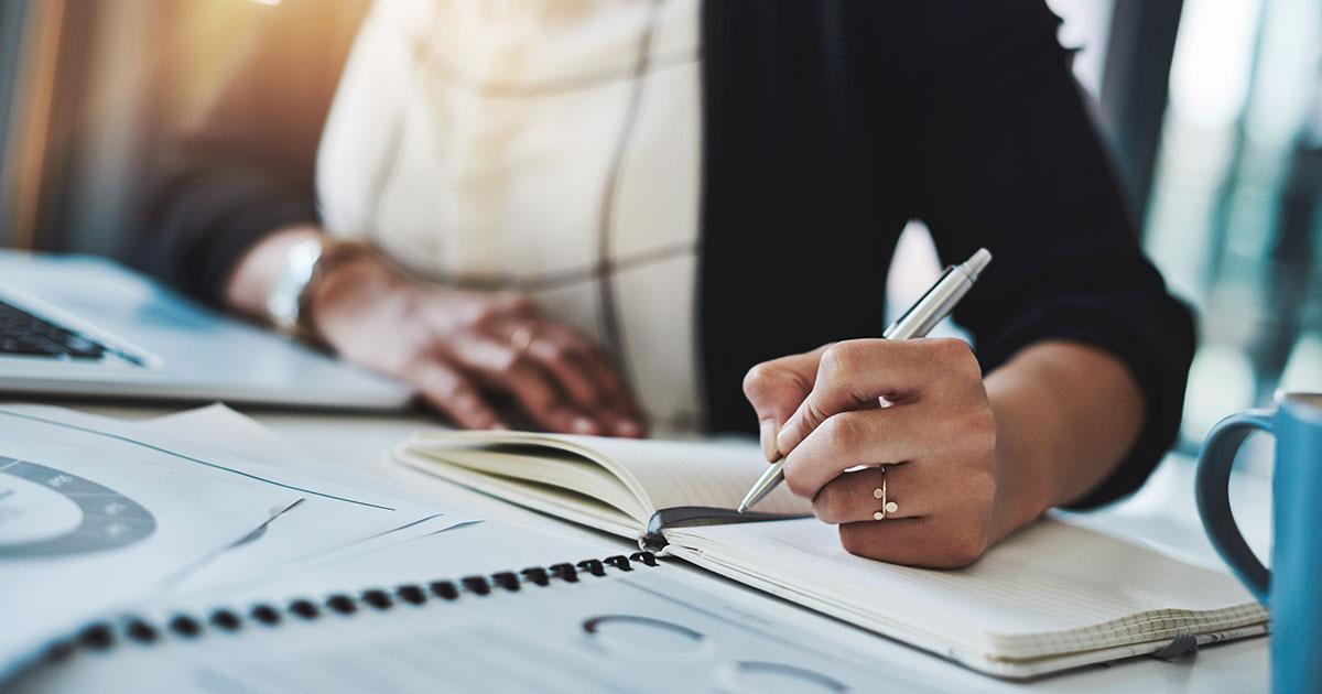 Händer som skriver med en bläckpenna i en anteckningsbok