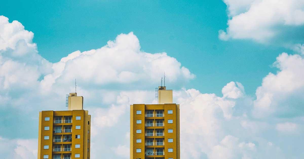 Två höghus med blå himel och vita moln i bakgrunden