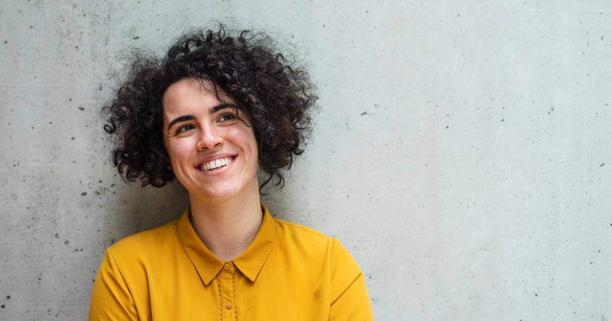 Person i gul blus med lockigt hår och leende vid betongvägg